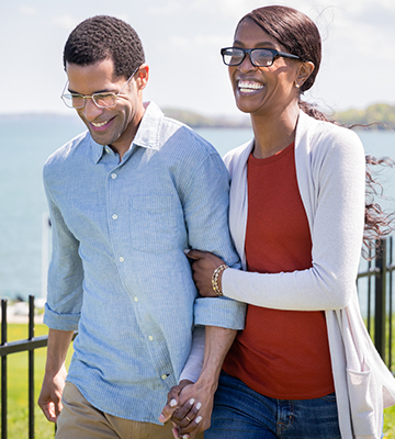 Couple linking arms walking and smiling