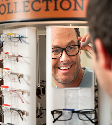 Man putting on glasses in a mirror